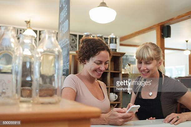 female shop assistants looking at smartphone in country store - heshphoto foto e immagini stock