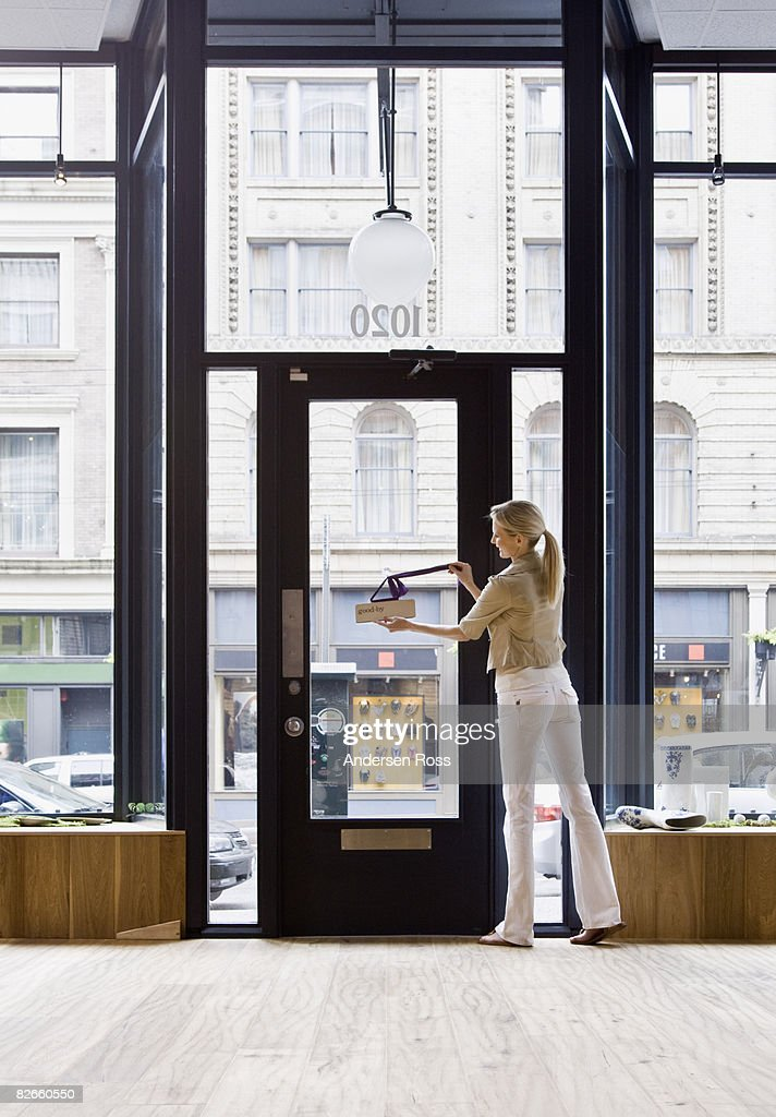 Female shop keeper posting a sign on the door & Door Keeper Stock Photos and Pictures | Getty Images