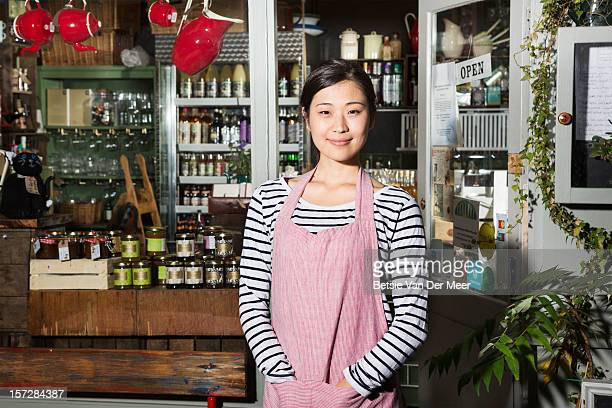 Female shop keeper standing in front of shop.