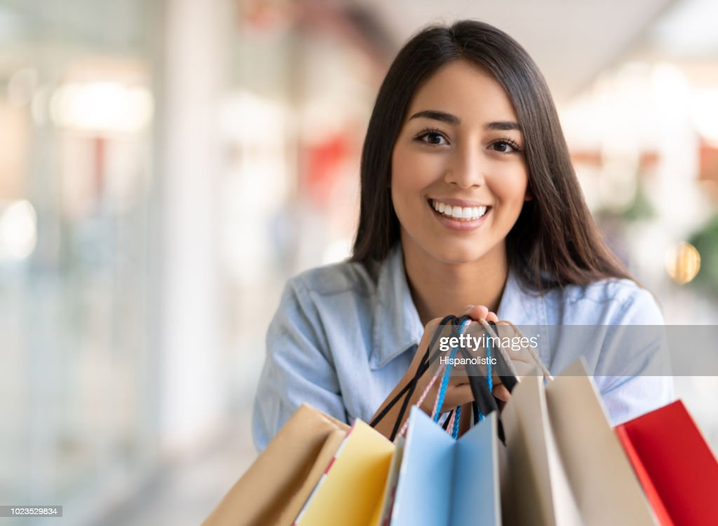 Female shopaholic at the mall excited and looking at camera while holding shopping bags : Stock Photo