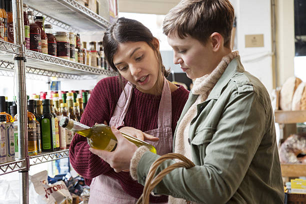 Female shopper asks advice to shop assistant on olive oil in organic delicatessen shop.
