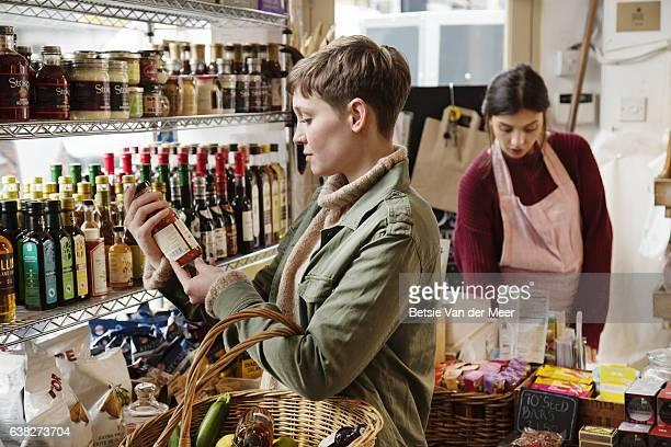 Female shopper checks label on tomato sauce bottle in organic delicatessen shop.