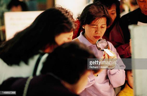 a female shopper inspecting a gemstone with a magnifying glass at the jade market in yaumati - visual china group stock pictures, royalty-free photos & images