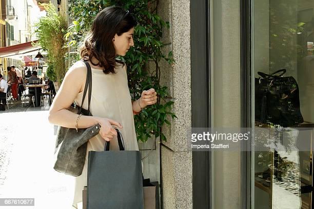 female shopper looking down at shop window, milan, italy - down blouse stock-fotos und bilder