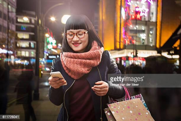 female shopper looks at digital device in city.