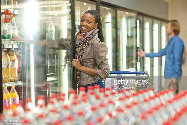 Female shopper reaching for soft drink from cooler