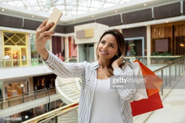cliente feminino tomando um selfie no shopping - photo messaging - fotografias e filmes do acervo