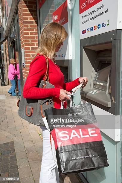 Female shopper using a cash dispenser machine at a high street bank