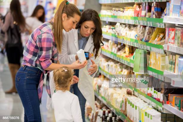 female shopper with daughter in supermarket - juice carton stock photos and pictures