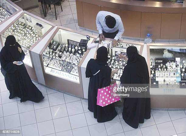 Female shoppers wearing traditional Saudi Arabian dress browse watches on sale at a luxury concession stand inside the Kingdom Centre shopping mall...