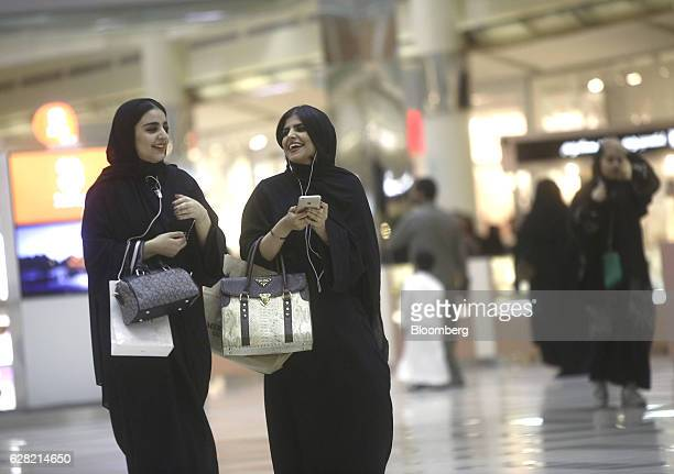 Female shoppers wearing traditional Saudi Arabian dress carry luxury designer handbags by Calvin Klein Inc left and Prada SpA as one checks her Apple...