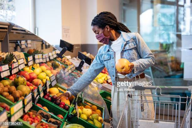 female shopping fruits in grocery shop - fruit stock pictures, royalty-free photos & images