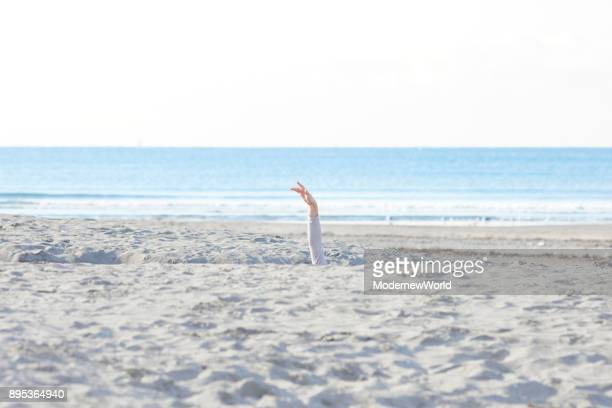A female showing her hand from the sand pit on the beach in the morning