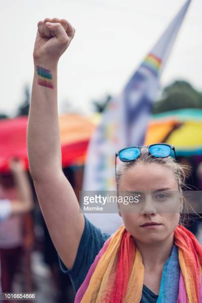 Female showing rainbow tattoo with her fist clenched high up