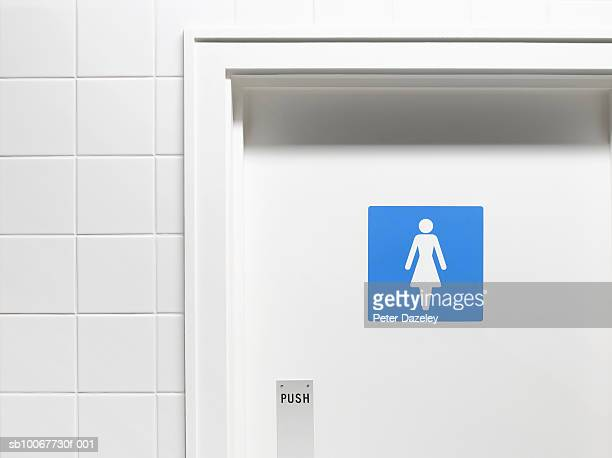 Female sign on toilet door, close-up