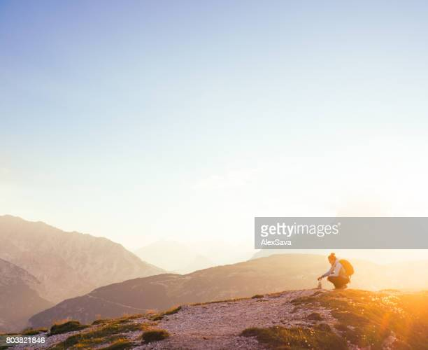 Female silhouette finding her inner peace in breathtaking mountain environment during sunrise