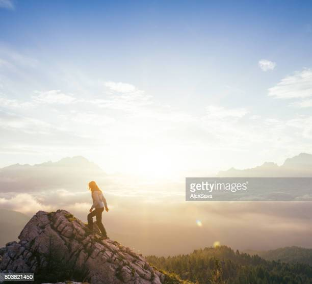 Female silhouette on top of mountain peak during sunrise