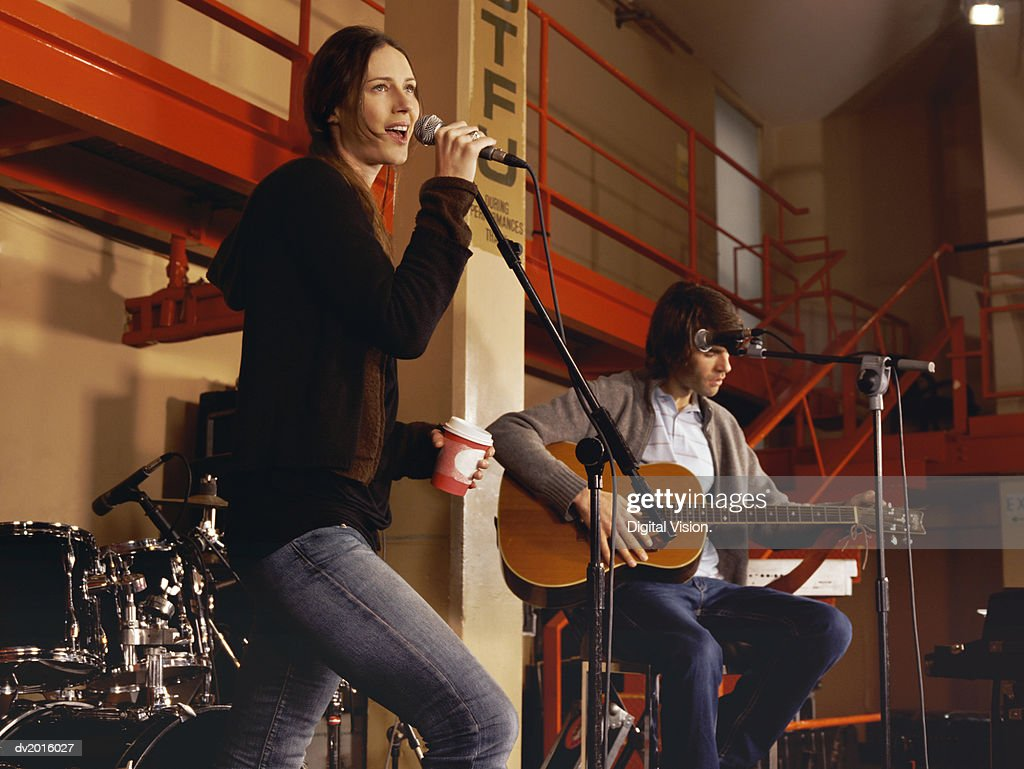 Female Singer and Male Guitarist Rehearsing on Stage : Stock Photo