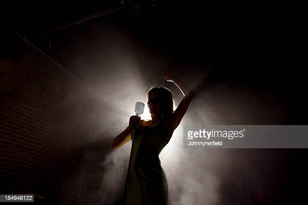 female singer backlit on a smokey stage - diva human role stock photos and pictures