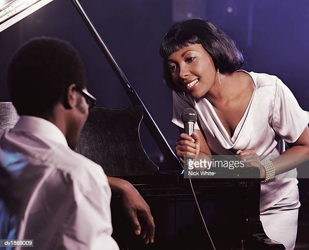 Female Singer in a Nightclub Holding a Microphone and Singing to a Pianist