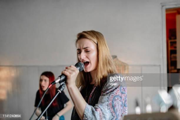 彼女のバンドとリハーサルの女性歌手 - シンガーソングライター ストックフォトと画像