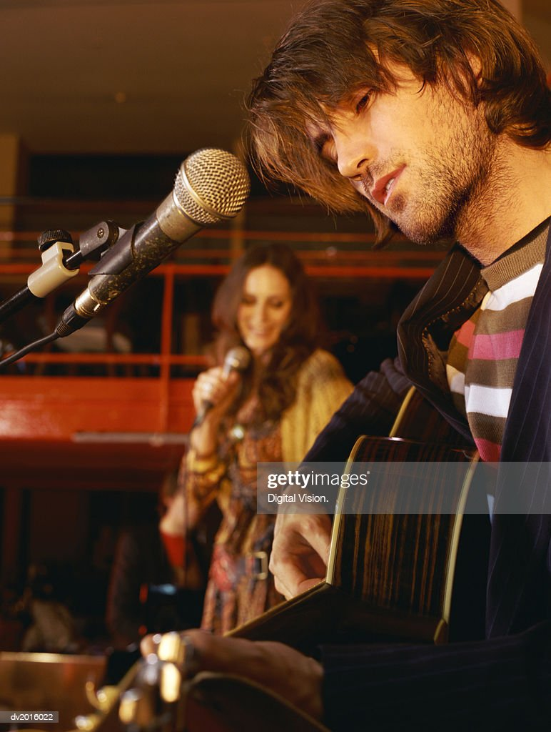 Female Singer Performing on Stage With a Male Guitarist : Stock Photo