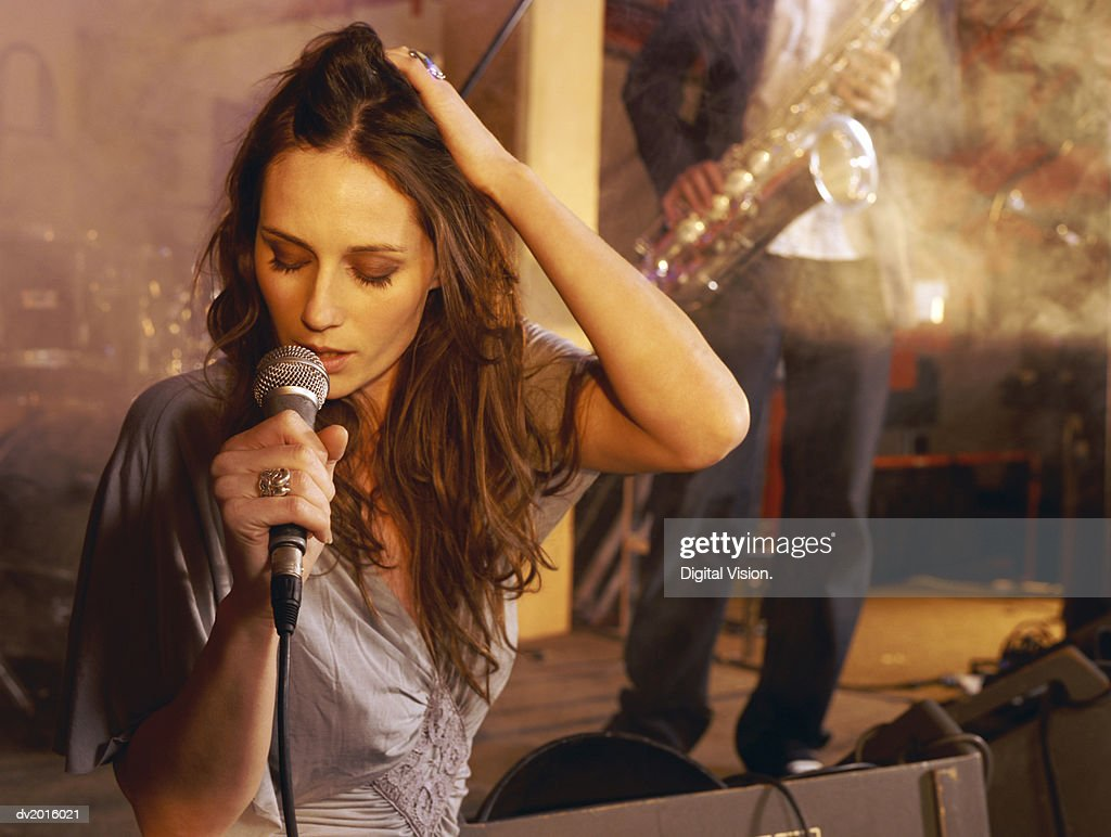 Female Singer Performing on Stage With a Man in the Background Playing a Saxophone : Stock Photo