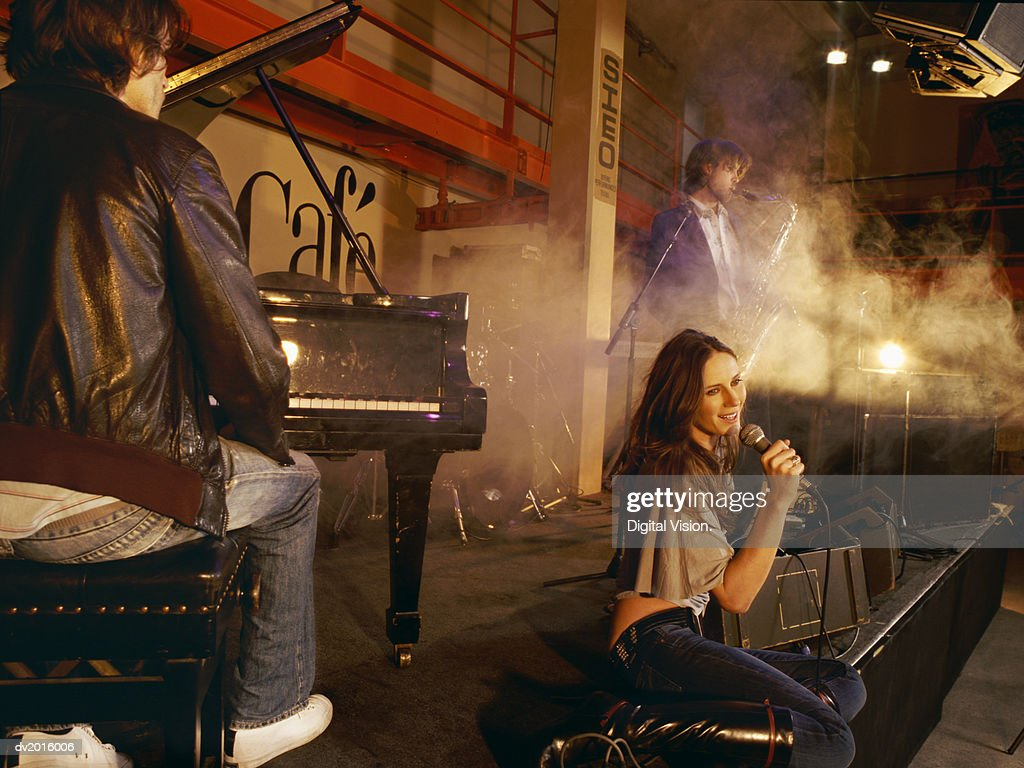 Female Singer Performs on Stage With a Male Pianist and Saxophonist : Stock Photo