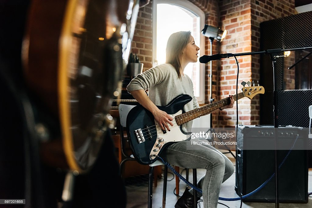 Female singer playing guitar and performing a song : Stock Photo