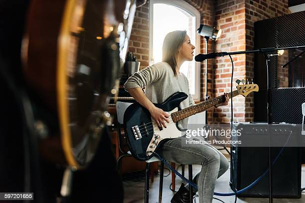 female singer playing guitar and performing a song - chanteur photos et images de collection