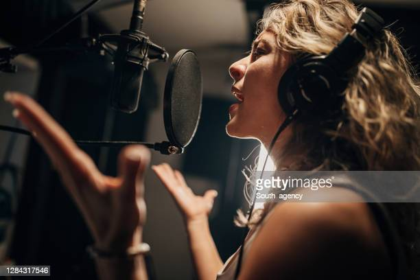female singer recording song in music studio - pop musician stock pictures, royalty-free photos & images