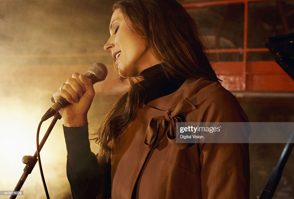 Female Singer Singing into a Microphone on a Smokey Stage : Stock Photo