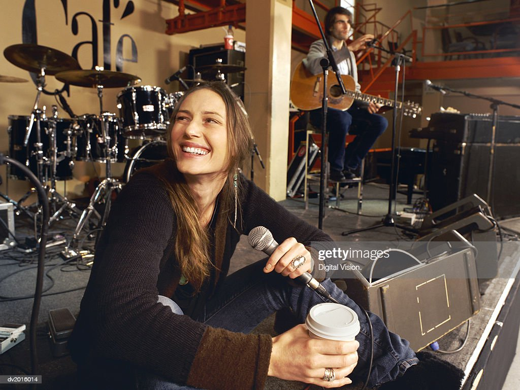 Female Singer Sits on a Stage Having a Coffee Break at a Gig Rehearsal : Stock Photo