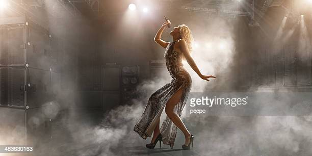 Female singer with microphone, floodlights, and smoke effect