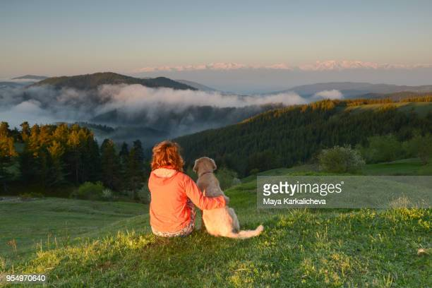 female sitting by a golden retriever dog in a mountain valley - plovdiv imagens e fotografias de stock