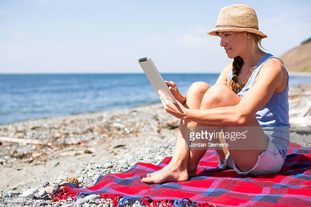 A female sitting on a blanket and using an iPad.