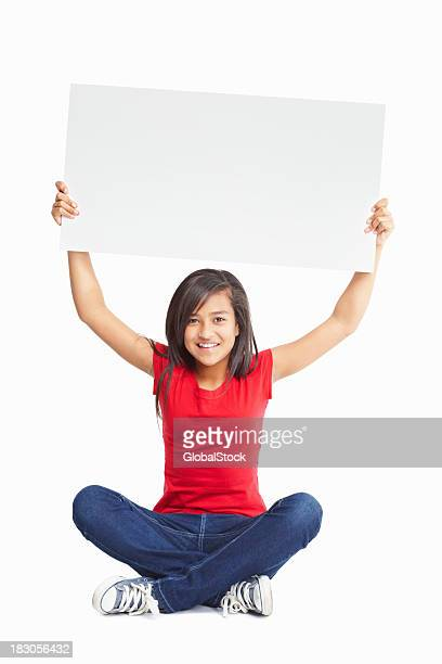 Female sitting on floor as she holds up a billboard