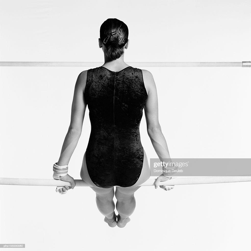 Female sitting on uneven bars, rear view, b&w. : ストックフォト
