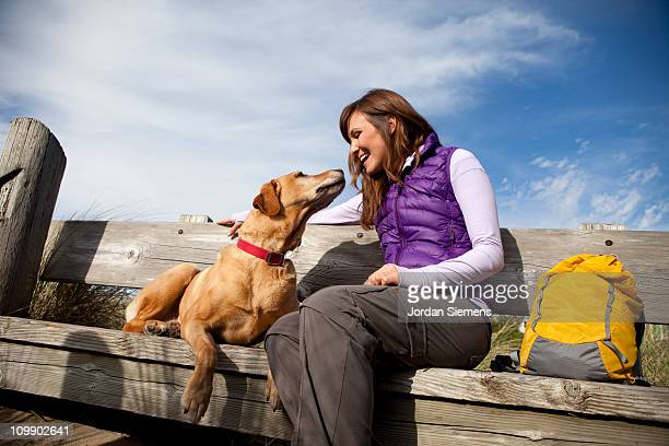 A female sitting with her dog.