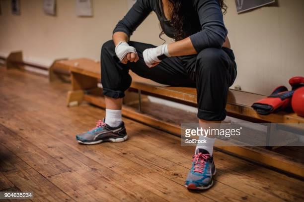 女性のボクシングのために包まれた両手で座っています。