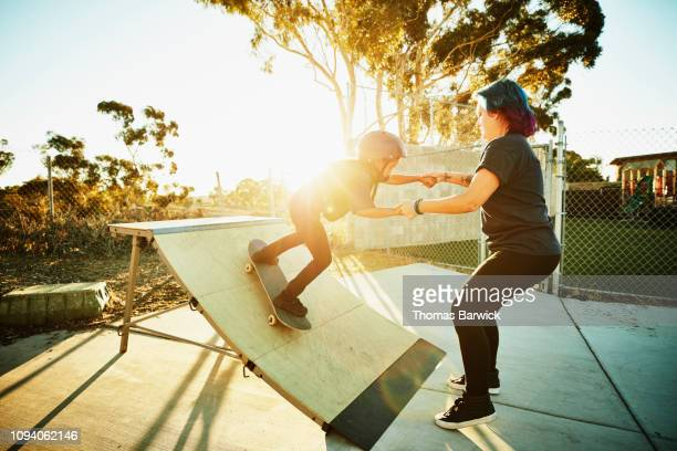 female skateboard instructor helping young female student ride ramp during skate camp - california strong stock photos and pictures