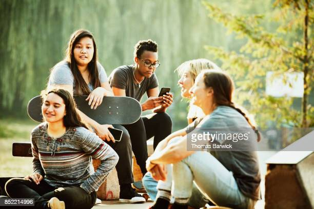 Female skateboarder looking at smartphone while hanging out with friends in skate park
