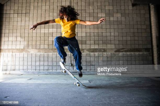 female skateboarder performing jump in warehouse environment - skating stock pictures, royalty-free photos & images