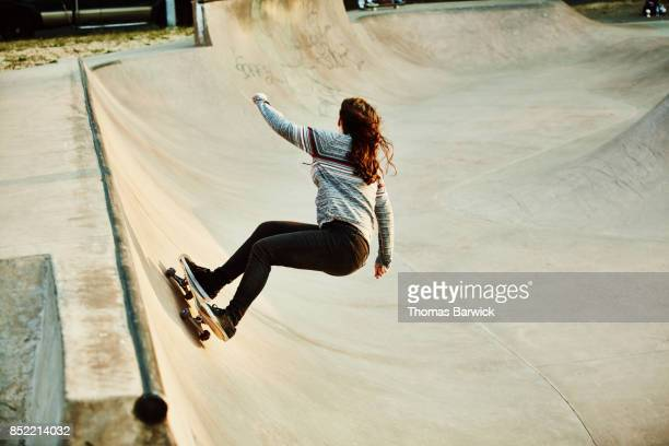 female skateboarder playing in bowl in skate park on summer morning - girl power stock photos and pictures
