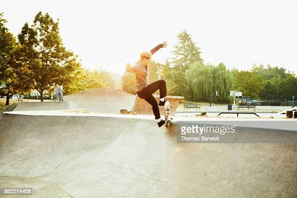 Female skateboarder preforming trick while skating in skate park on summer morning