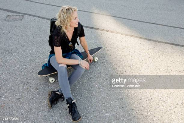 female skateboarder sitting on skateboard - skinny jeans stock pictures, royalty-free photos & images