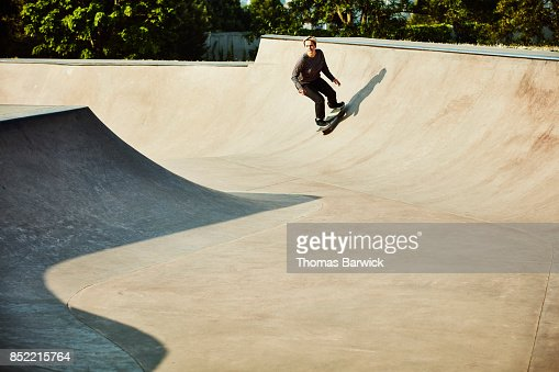Female skateboarder skating bowl in skate park