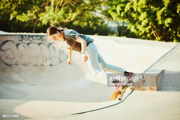 Female skateboarder skating in bowl in skate park on summer morning