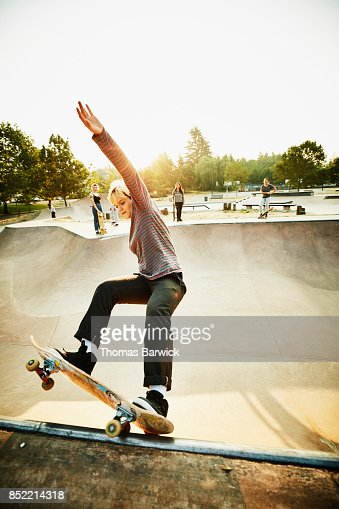 Female skateboarder skating in skate park bowl on summer morning