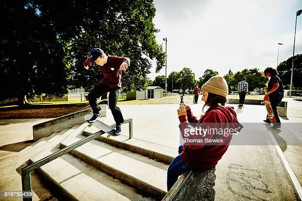 Female skateboarder taking video on smartphone